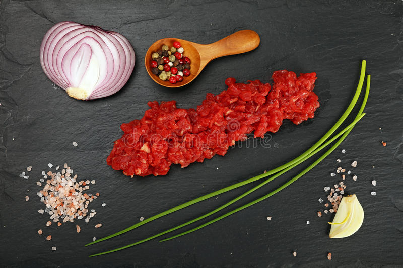 Raw beef minced meat and spices on black board stock photo