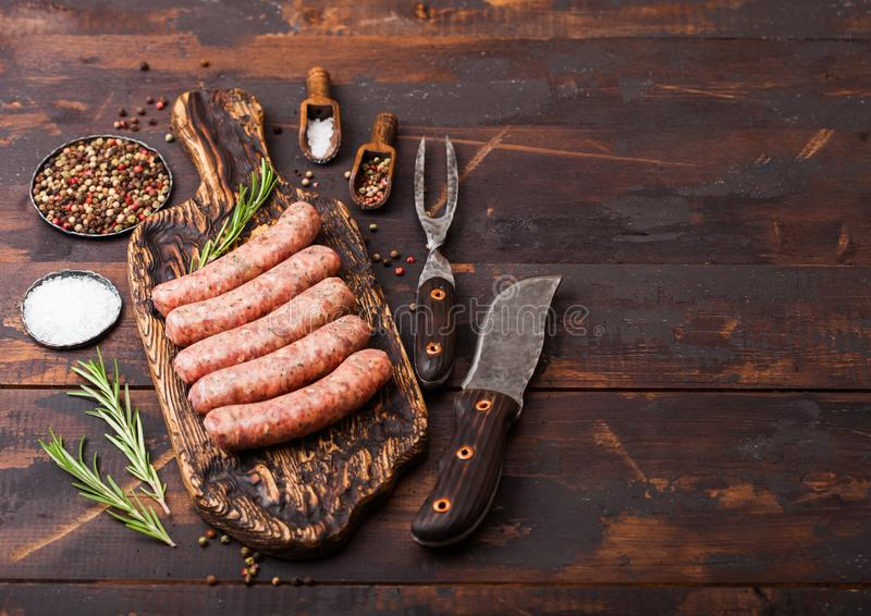 Raw beef and pork sausage on old chopping board with vintage knife and fork on dark wooden background.Salt and pepper with royalty free stock images
