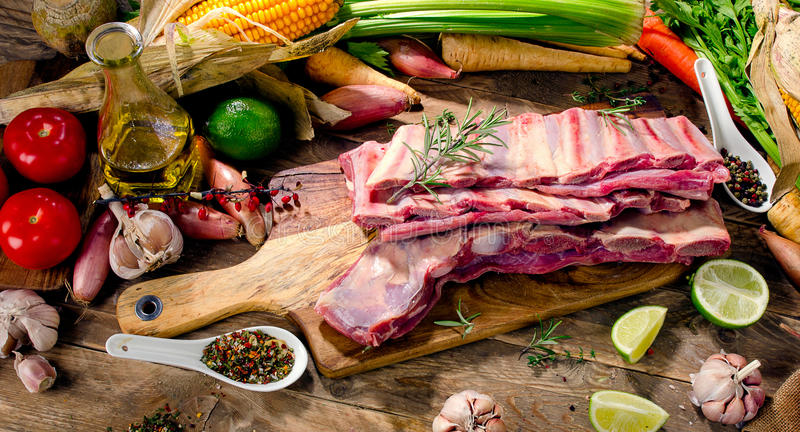 Raw beef ribs and vegetables on a dark wooden background. View from above royalty free stock photography