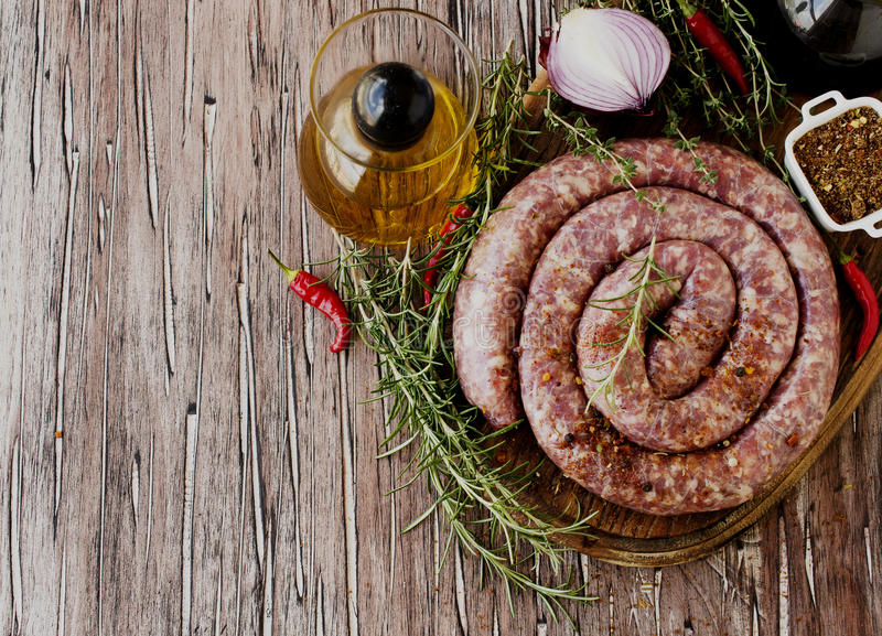 Raw beef sausages on a cast-iron pan, selective focus. Raw beef sausages on a cast-iron pan with rosemary and spices on a wooden table, South African boerewors royalty free stock photo