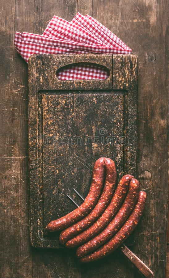 Raw beef sausages for grill or bbq on dark vintage cutting board with meet fork and napkin on rustic wooden background, top view. stock image