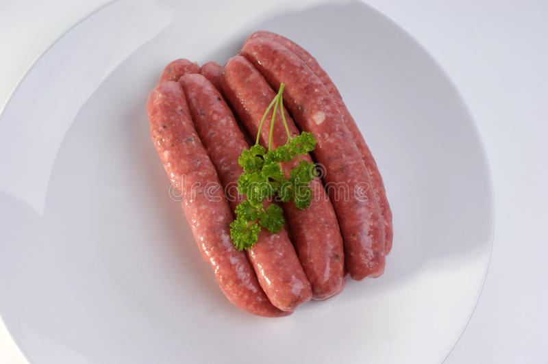 Raw beef sausages on a timber board royalty free stock images