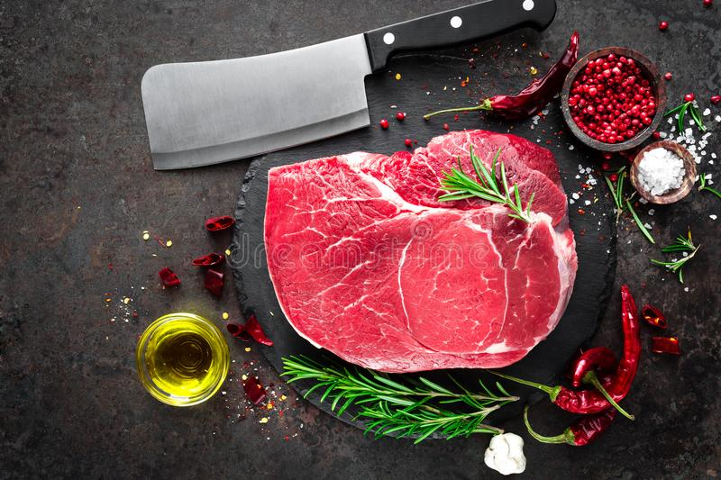 Raw beef steak on black background with cooking ingredients. Fresh beef meat stock photography