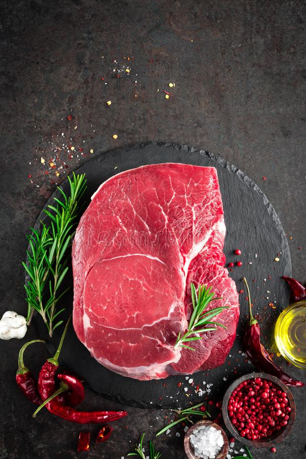 Raw beef steak on black background with cooking ingredients. Fresh beef meat. Top view stock photos