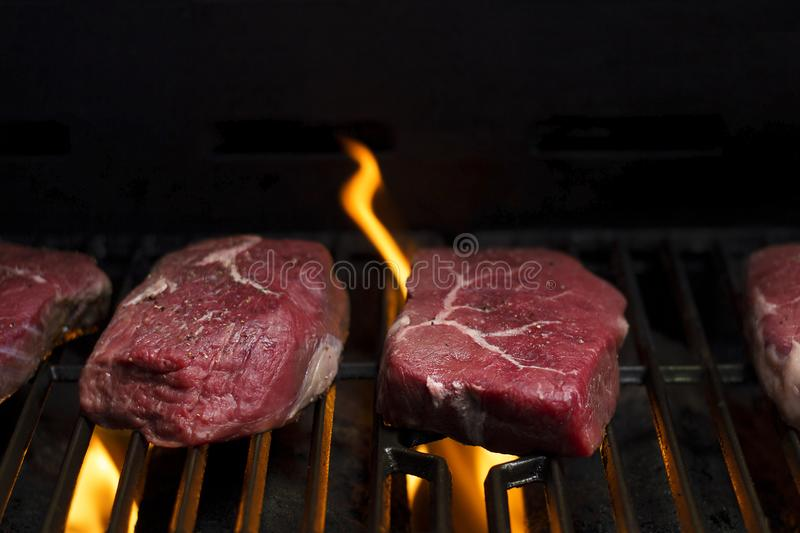 Raw beef steak cooking over flaming grill royalty free stock photos
