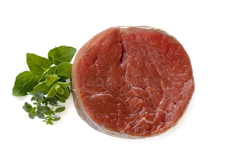 Raw Beef Steak with Herbs Isolated. Raw beef steak with fresh herbs, isolated on white. Overhead view stock images