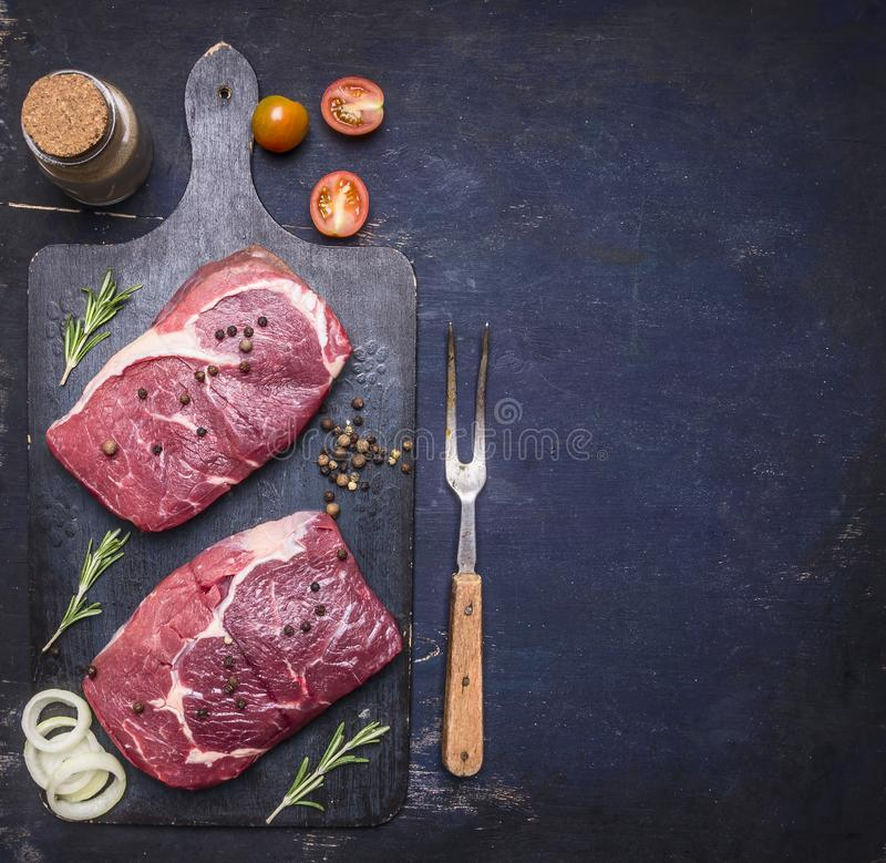 Raw beef steak with rosemary,butter and meat fork on dark rustic cutting board, top view with space for tex. T royalty free stock photos