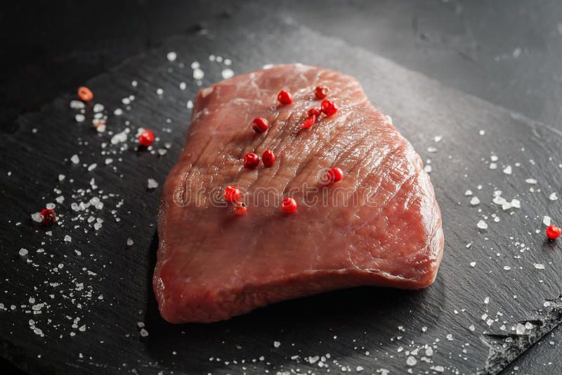 Raw beef steak with rosemary and peppers on dark stone. Raw beef steak with rosemary and peppers on a dark stone royalty free stock image