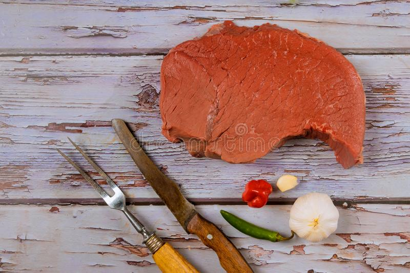 Raw beef steak with spice knife, garlic pepper on wooden table royalty free stock photos