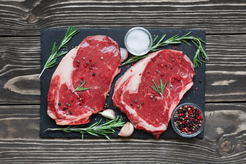 Raw beef steak with spices and rosemary on black slate board over wooden background stock images