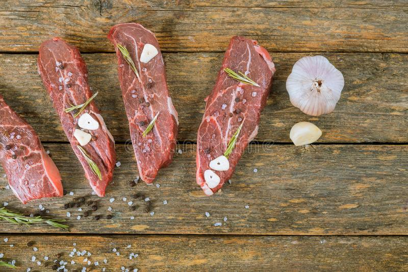 Raw beef steak on a wooden table. With rosemary and garlic, ribeye, mignon, uncooked, fillet, pepper, protein, dinner, board, sirloin, ingredient, cut royalty free stock photography