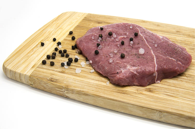 Raw beef steak from young bull with salt and pepper on cutting board. On white isolated background royalty free stock photo