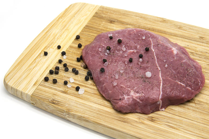 Raw beef steak from young bull with salt and pepper on cutting board. On white isolated background stock photos