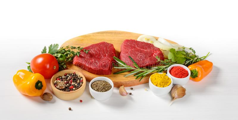 Raw beef steaks on a cutting board with spices stock images