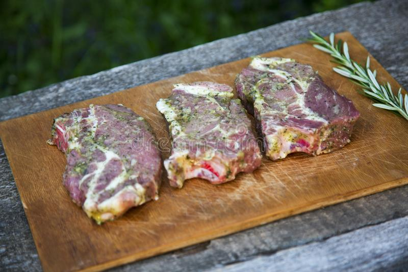 Raw beef steaks ready for cooking with spices on wooden board. S. Ide view stock image