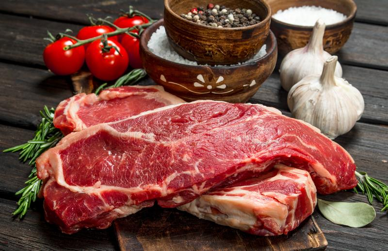 Raw beef steaks with salt and spices stock photos