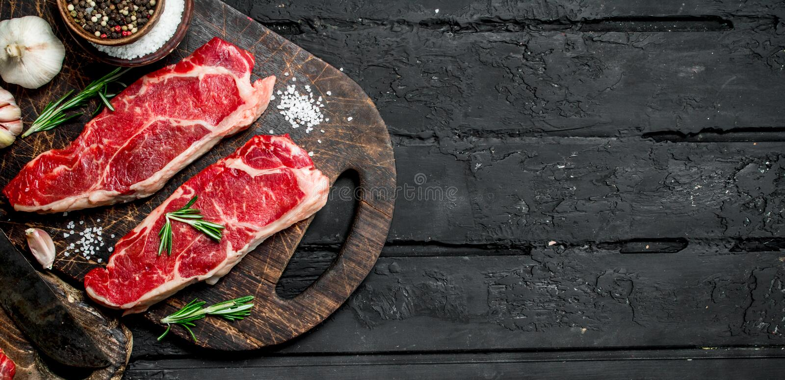 Raw beef steaks with spices stock photos