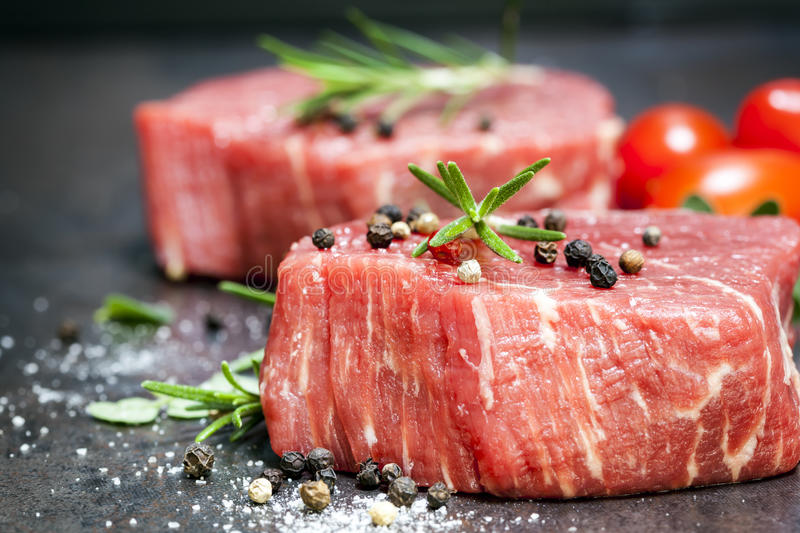 Raw Beef Steaks with spices and Rosemary over Slate. Raw beef steaks with spices, herbs and cherry tomatoes, over dark slate royalty free stock photo