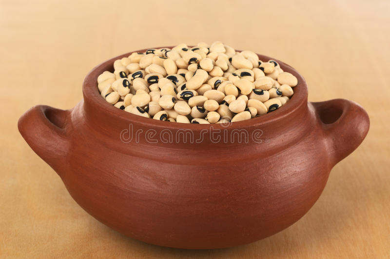 Raw Black-Eyed Peas in Rustic Bowl. Raw black-eyed peas (cowpeas) in rustic bowl photographed on wood (Selective Focus, Focus on the peas in the front of the royalty free stock images