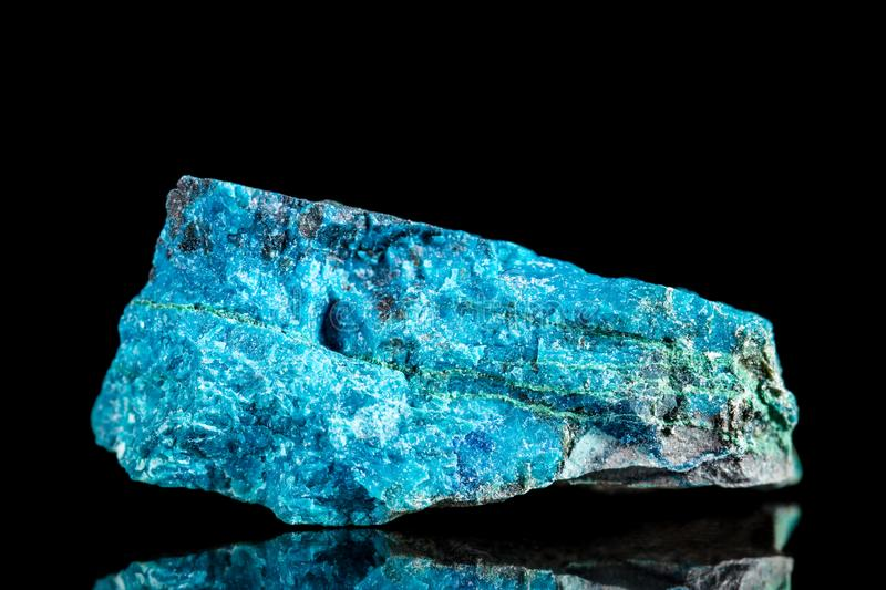 Raw blue apatite mineral stone in front of black background royalty free stock photography