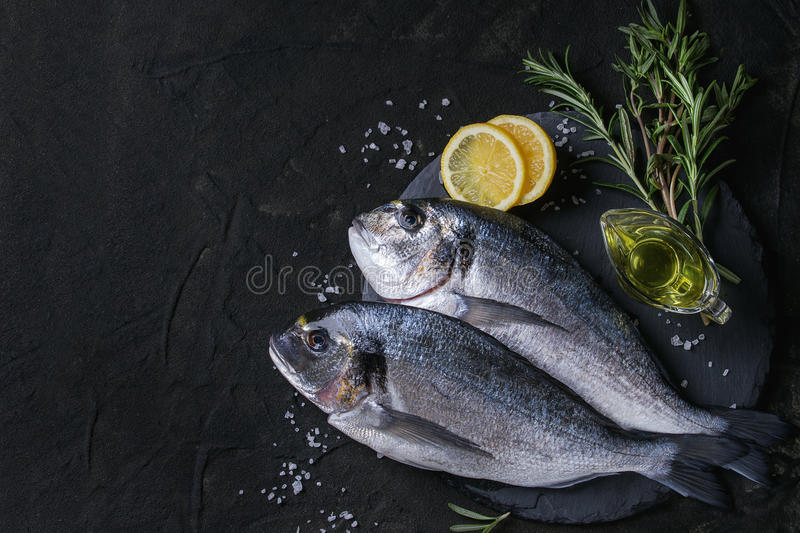Raw bream fish with herbs. Two ready to cook raw bream fish with herbs, lemon and olive oil on stone slate board over black textured background. With copy space stock images