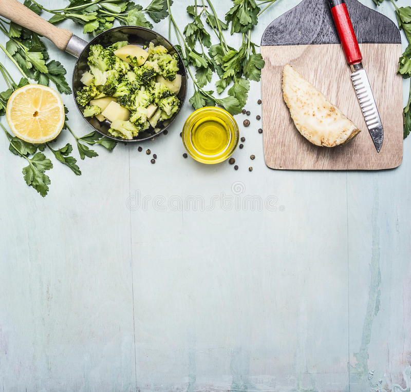 Raw broccoli in a pan with herbs, lemon, celery root on a cutting board with a knife border ,place text on wooden rustic backg. Raw broccoli in a pan with herbs royalty free stock image
