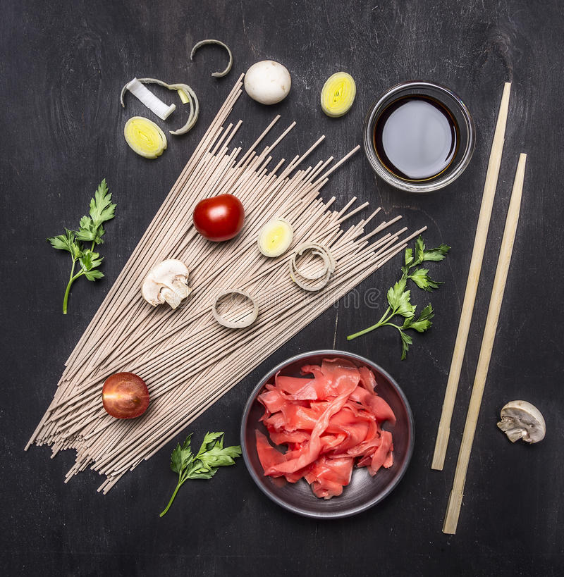 Raw buckwheat noodles, pickled ginger, onion, chopped pepper, chopsticks, soy sauce, ingredients for cooking Asian food border o. Raw buckwheat noodles, pickled royalty free stock photo