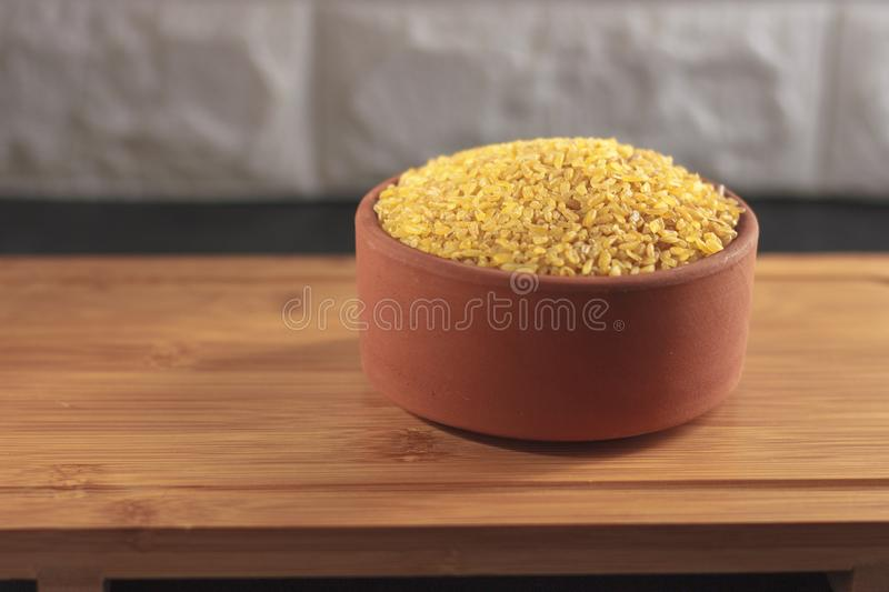Raw bulgur in a clay bowl on a wooden board royalty free stock photography