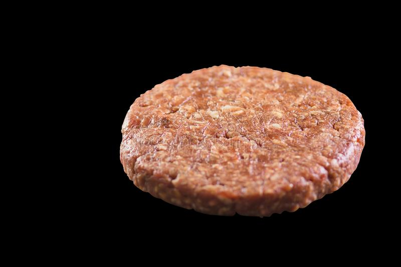 Raw burger cutlet on a black background close-up stock photos