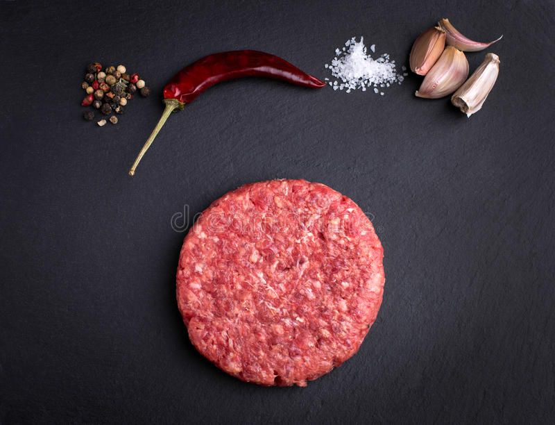 Raw burger with species. In a black background royalty free stock image