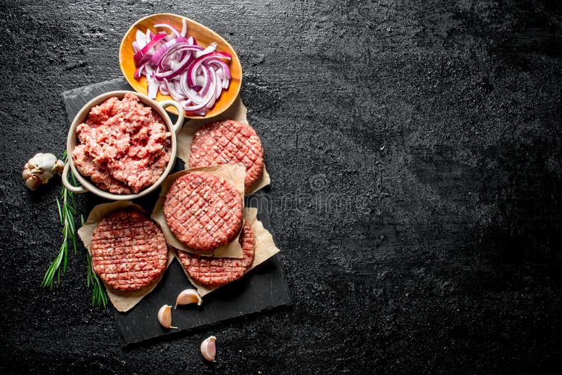Raw burgers with ground beef and sliced onions in bowls stock photos