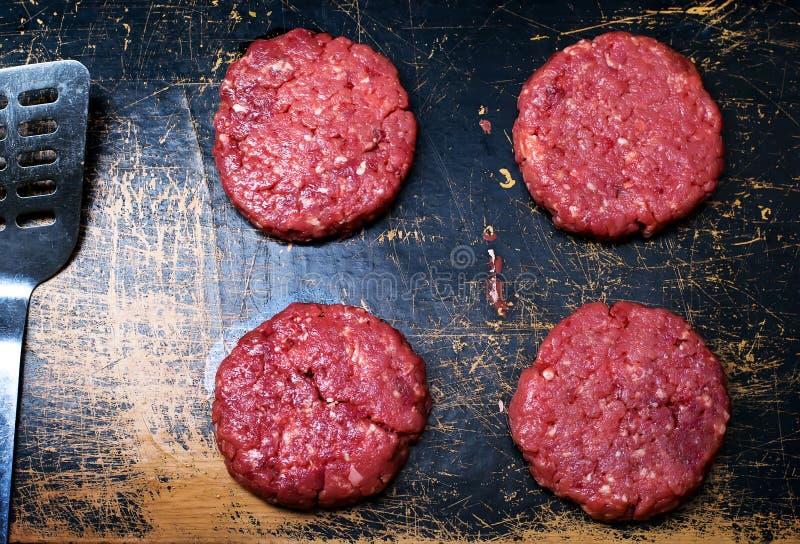 Raw burgers from organic beef stock image