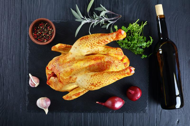 Raw butchered rooster on black stone tray. Raw butchered rooster with golden skin on black stone tray with ingredients for marinade and bottle of wine on wooden royalty free stock image
