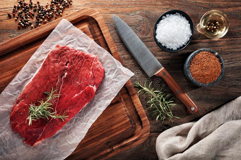 Raw calf beefsteak on white cooking paper and wooden cutting table royalty free stock photo