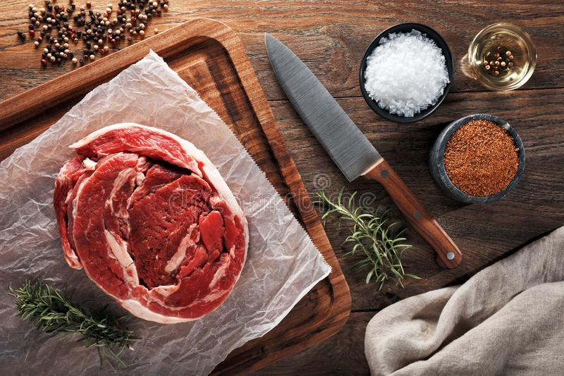 Raw calf brisket meat on white cooking paper and wooden cutting table. Dercorated with herbs, spices and chef knife. Raw calf brisket beef on white cooking paper royalty free stock photos