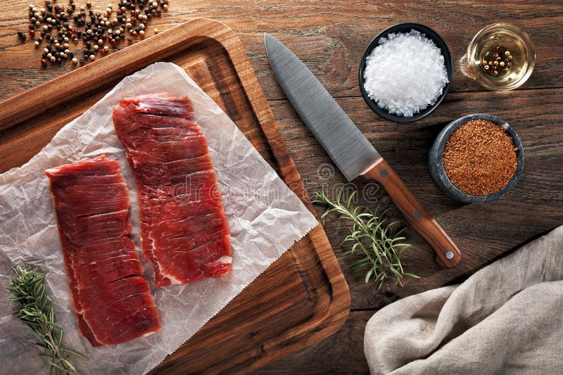 Raw calf flank beef on white cooking paper and wooden cutting table. Decorated with herbs, spices and knife. Raw calf flank beef on white cooking paper and royalty free stock image