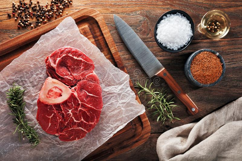 Raw calf shank beef with bone on white cooking paper and wooden cutting table. Decorated with herbs, spices and chef`s knife. Raw calf shank beef with bone on royalty free stock images
