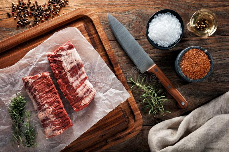 Raw calf skirt steak meat on white cooking paper and wooden cutting table stock image