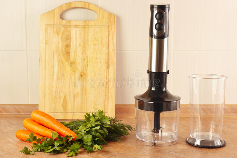 Raw carrots with herbs and a blender on kitchen table stock photography