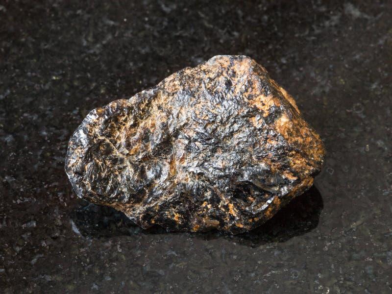 Raw Cassiterite Tin ore stone on black. Macro shooting of natural rock specimen - raw Cassiterite Tin ore stone on black granite background from Pravourmiyskoe royalty free stock photos