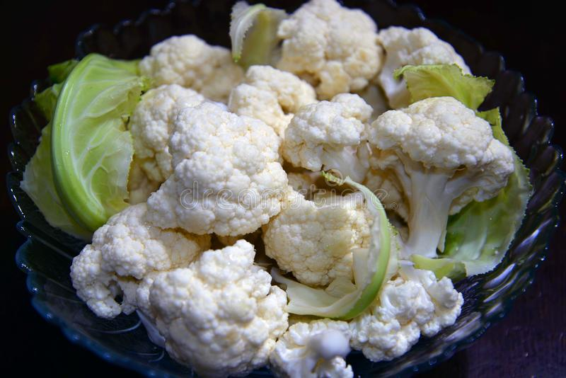 Raw cauliflower in the bowl. Fans of cooking use this ingredient in the preparation of delicious dishes stock images