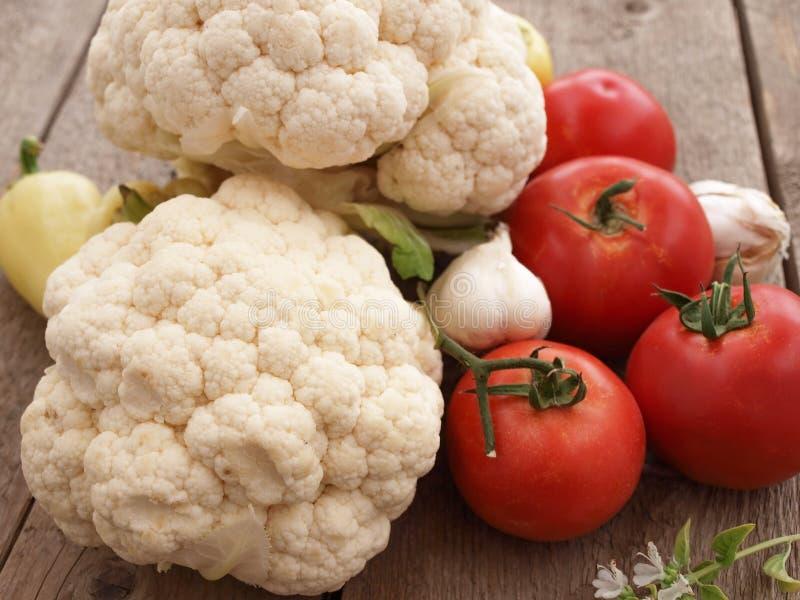 Raw cauliflower, tomatoes, garlic and pepper stock photo