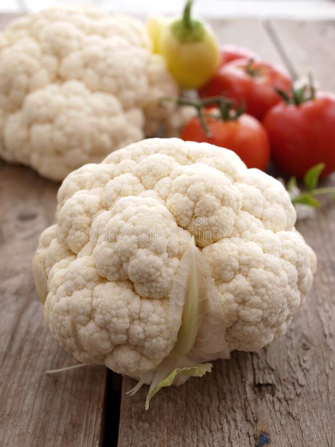 Raw cauliflower, whole vegetable on the plank surface stock photography