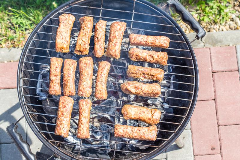 Raw cevapcici minced meat Ćevapčići on grill from southeastern Europe Balkan. Ready to be grilled stock photography
