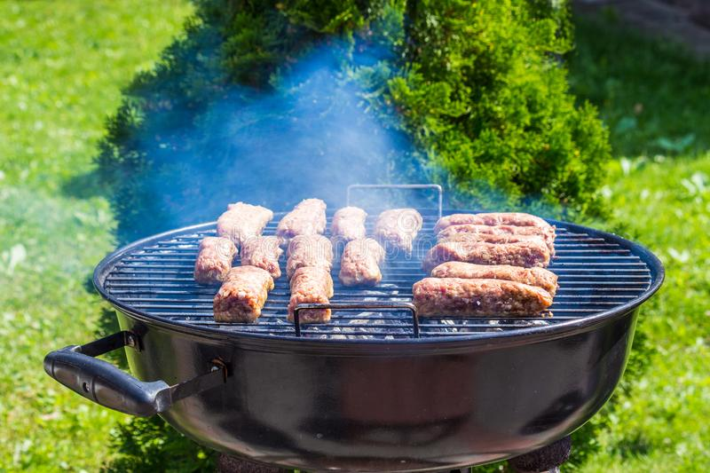 Raw cevapcici minced meat Ćevapčići on grill from southeastern Europe Balkan side view. Raw cevapcici minced meat Ćevapčići on grill from royalty free stock photo