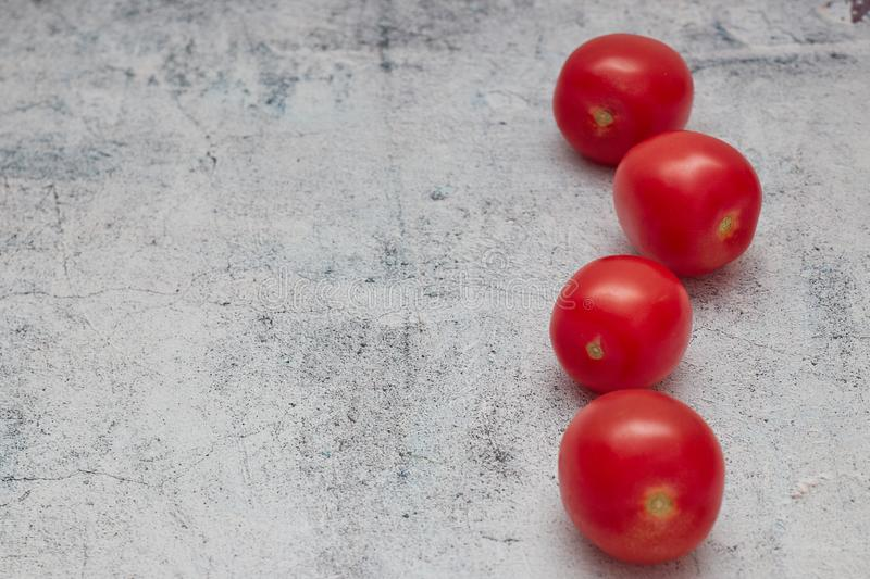 Raw cherry tomatoes on a light concrete background. horizontal view of red fresh cherries. copy space.close - up of a group of. Raw cherry tomatoes on a light stock photography