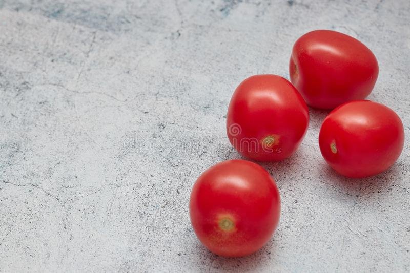Raw cherry tomatoes on a light concrete background. horizontal view of red fresh cherries. copy space.close - up of a group of. Raw cherry tomatoes on a light royalty free stock photography