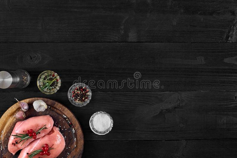 Raw chicken breast and condiments in a rustic wooden setting, top view stock photos