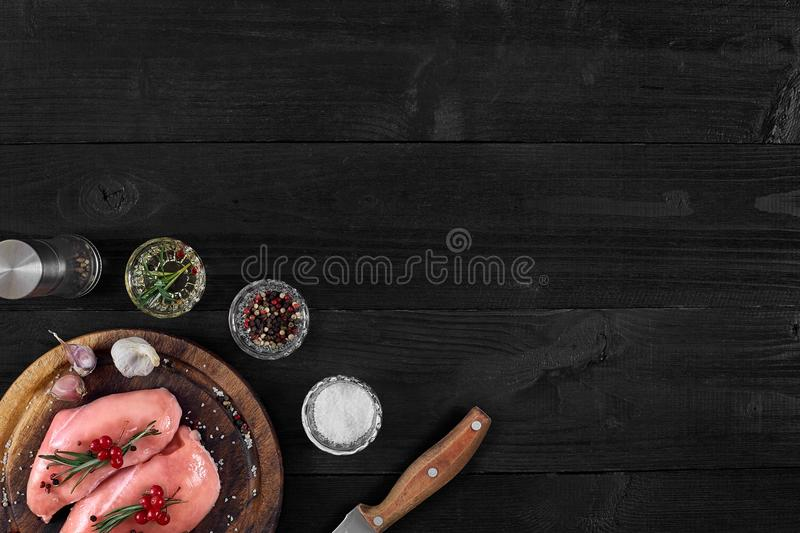 Raw chicken breast and condiments in a rustic wooden setting, top view royalty free stock photos