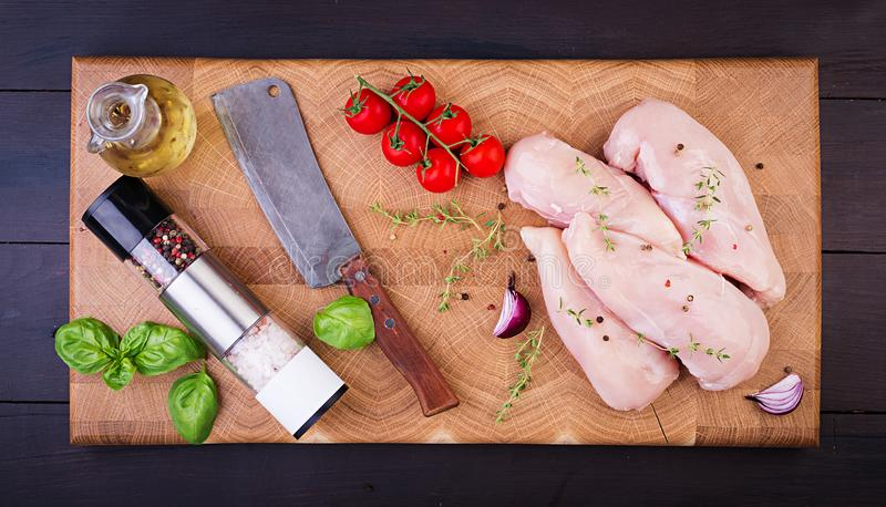 Raw chicken breast fillets on wooden cutting board with herbs and spices. royalty free stock photography